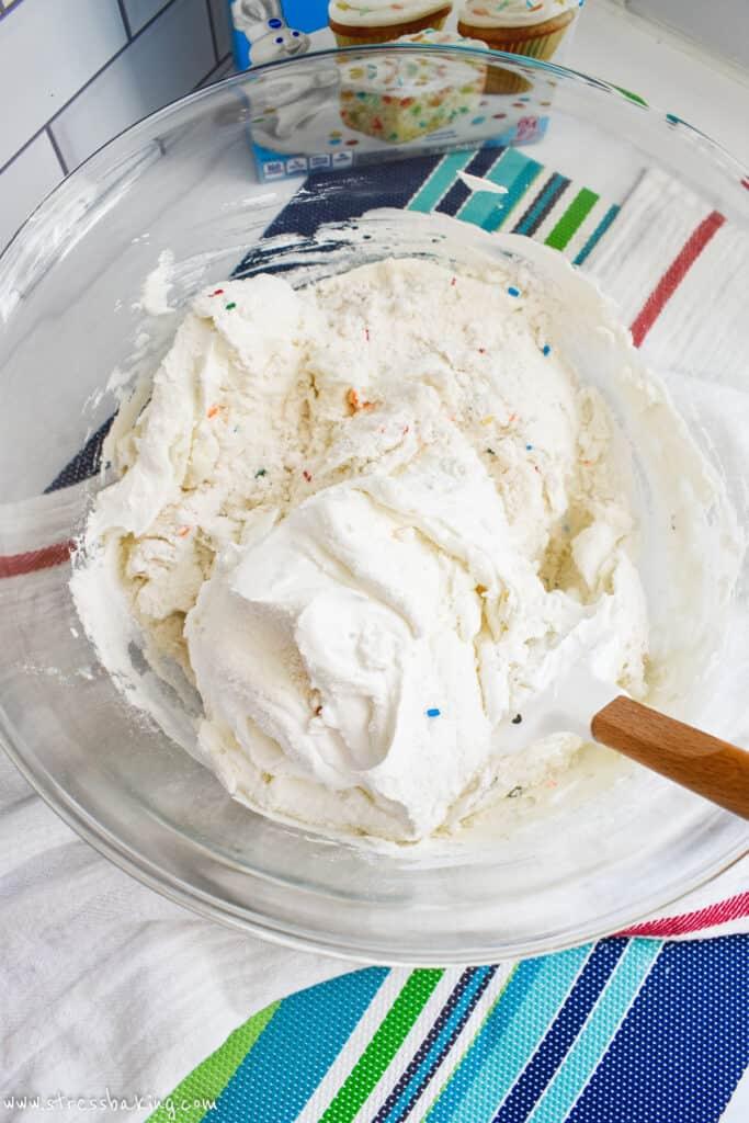 A mixing bowl full of funfetti cake mix, yogurt and cool whip
