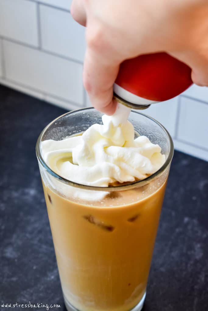 Whipped cream being piped onto a pint glass of mocha