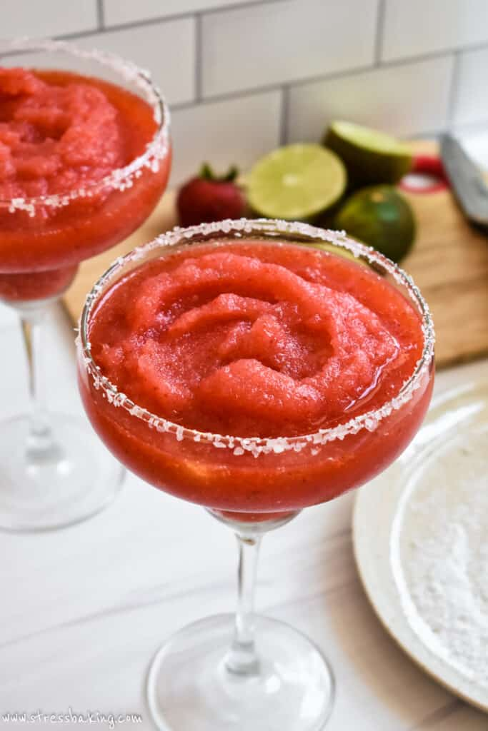 Bright red blended frozen strawberry margarita with a salted rim