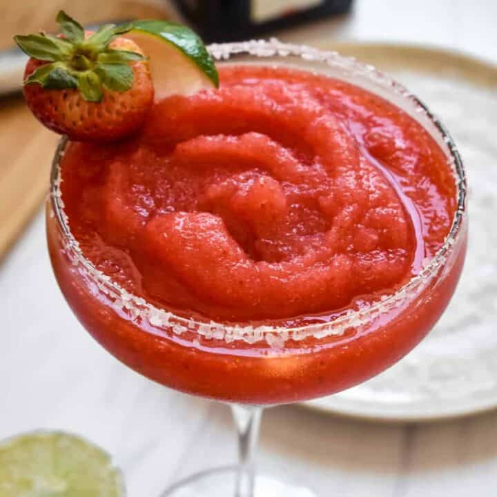A smooth, blended strawberry margarita with strawberry and lime garnish close up