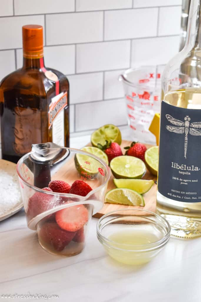 The ingredients for a strawberry margarita on a counter