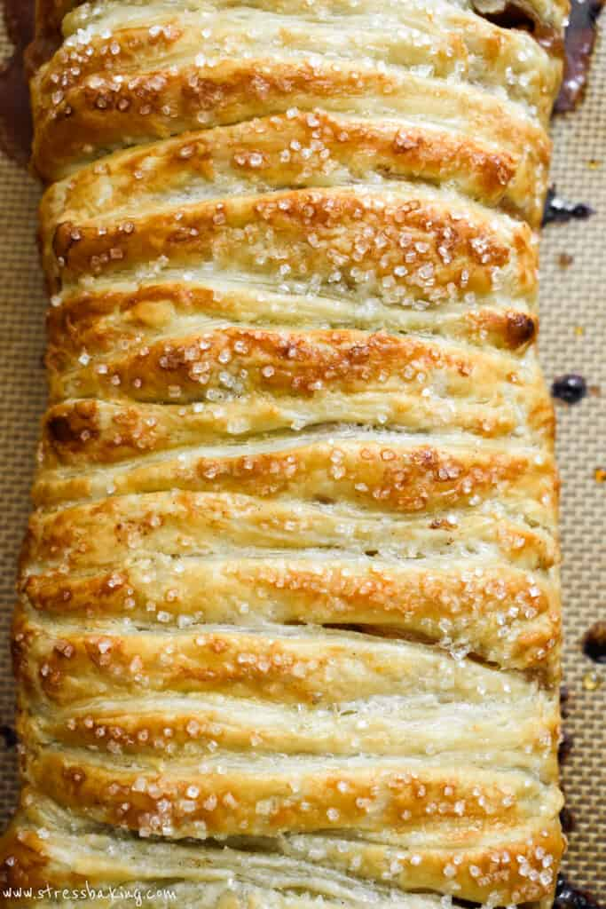 Golden pastry of braided apple strudel topped with sparkling sugar