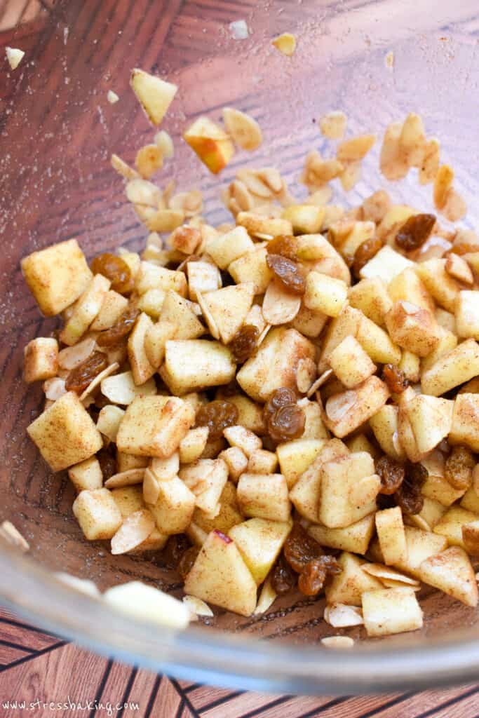 Diced apples and raisins coated in cinnamon sugar in a clear bowl
