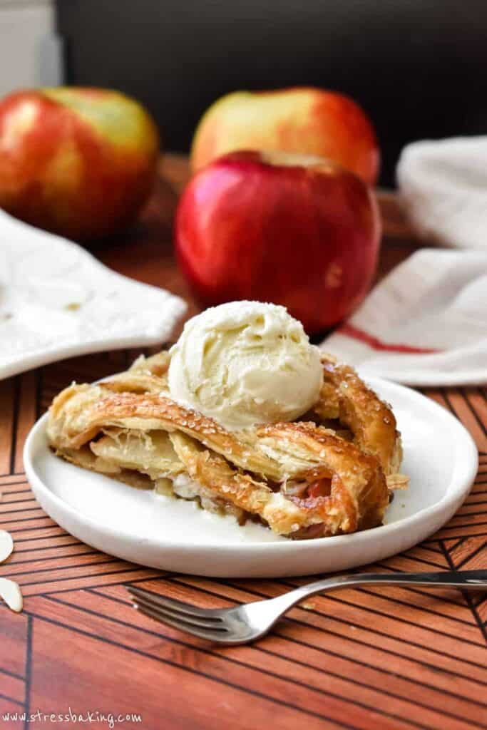 Slices of golden apple strudel on a small white plate with a scoop of vanilla ice cream on top