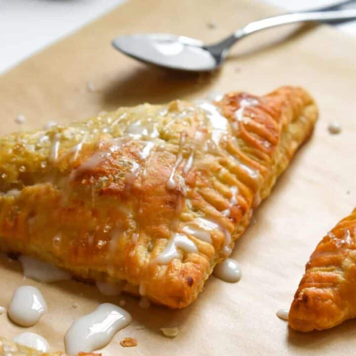 Closeup of apple turnovers on parchment paper drizzled with icing