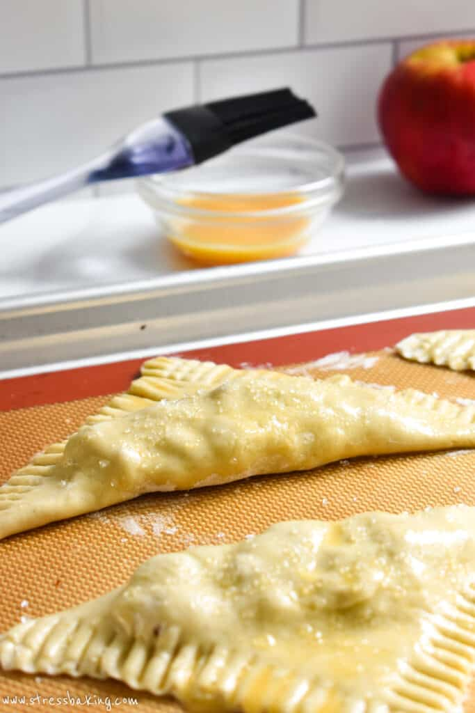 Turnovers coated with egg wash and sparkling sugar on a baking sheet