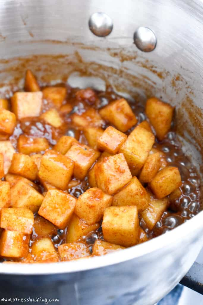 Cinnamon apple filling in a pot with bubbling syrup