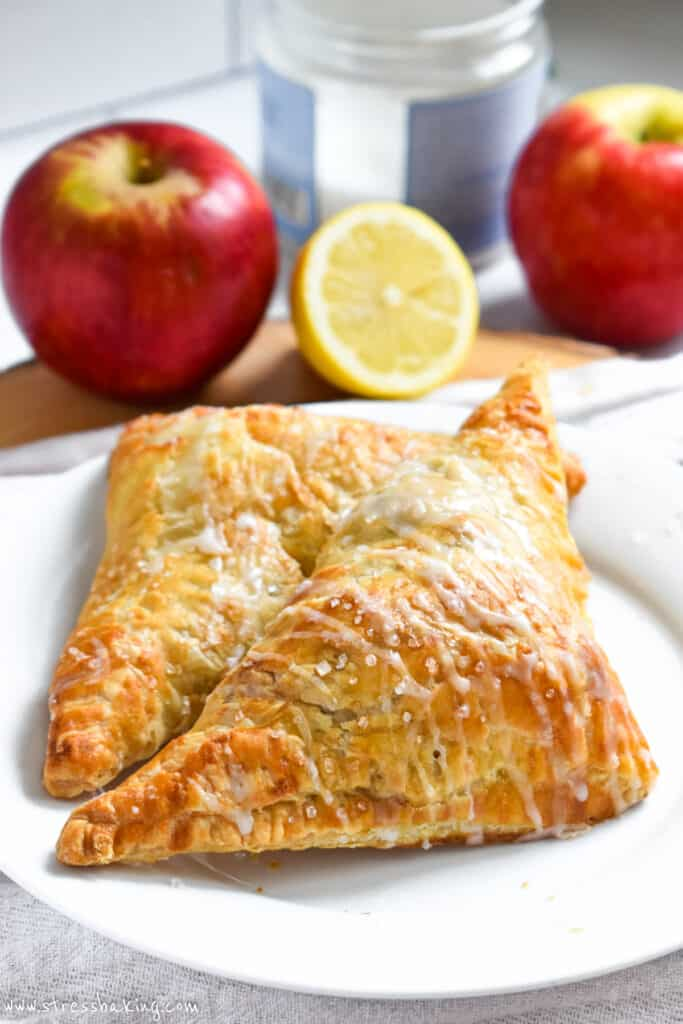 Two apple turnovers drizzled with glaze and sparkling sugar on a white plate