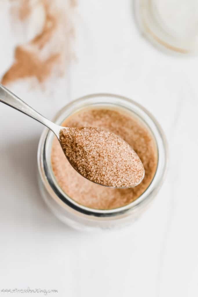 A small spoonful of cinnamon sugar above a glass jar on a white counter