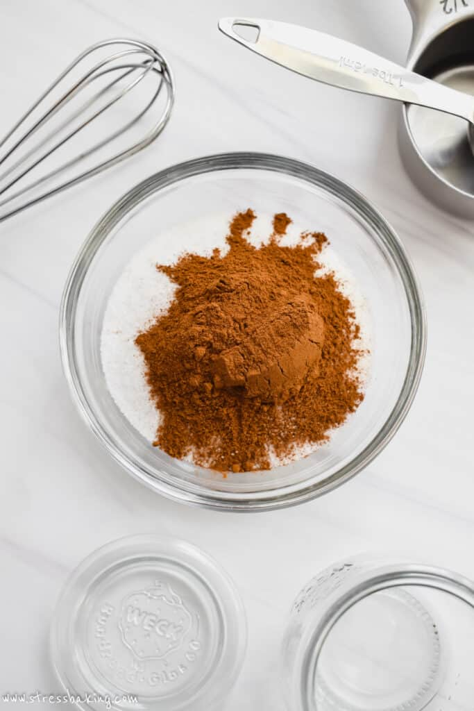 A glass bowl of cinnamon and sugar before being combined on a white counter