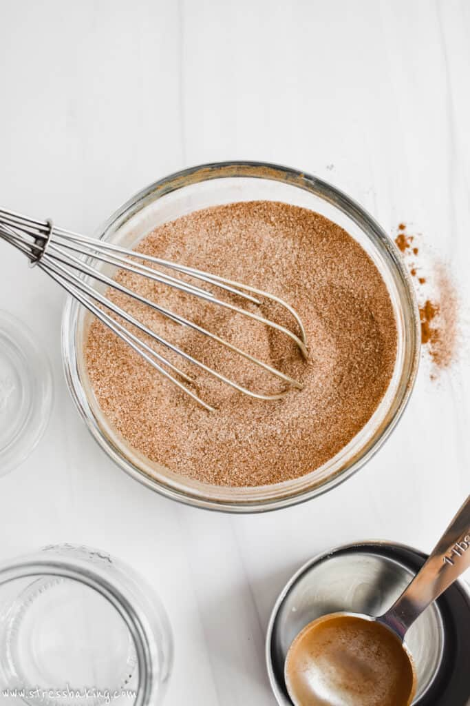 A glass bowl of cinnamon sugar with a whisk on a white counter