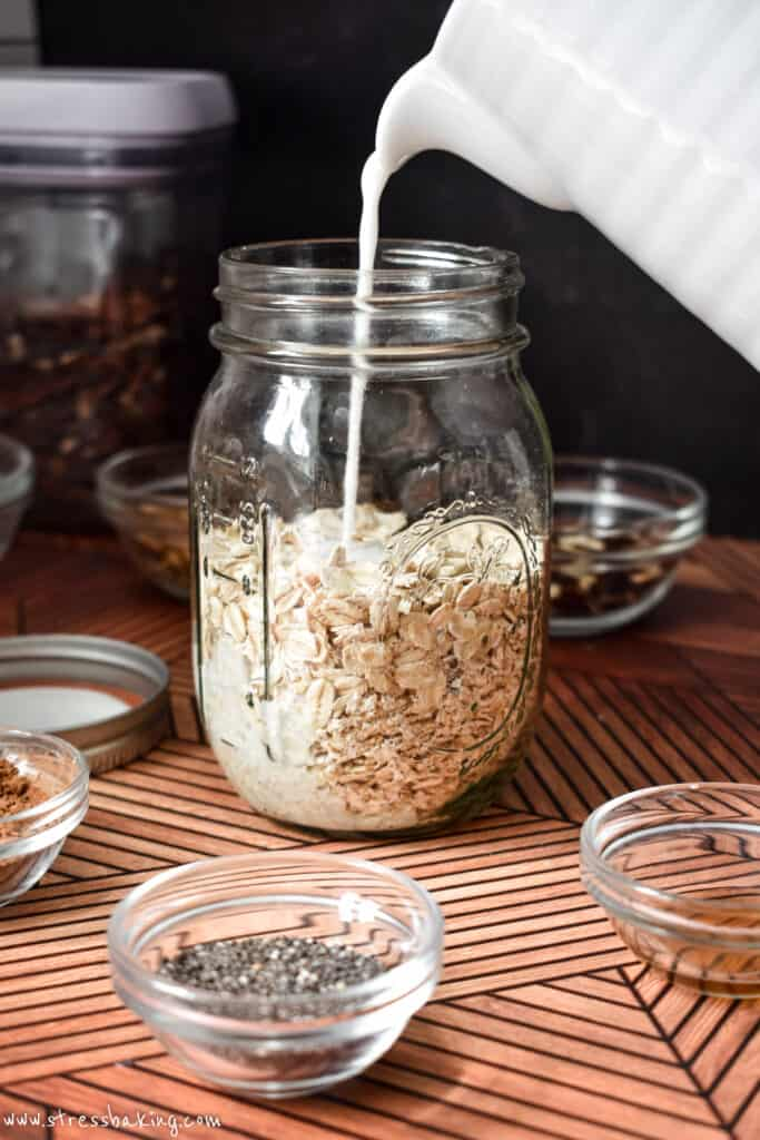 Milk being poured into a mason jar of oats