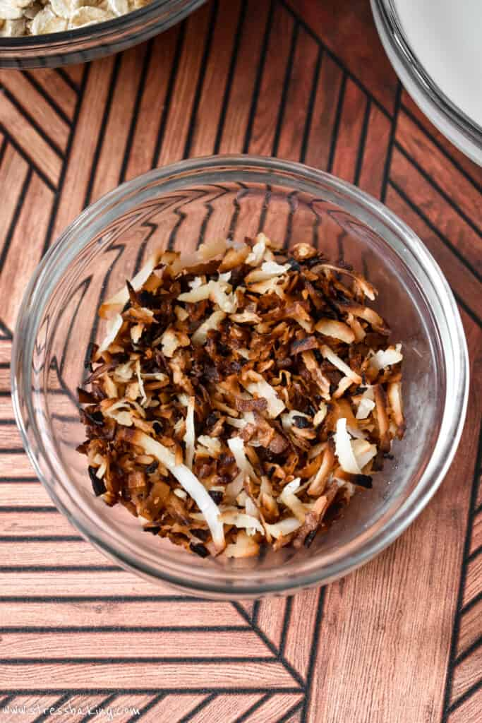 Toasted shredded coconut in a clear bowl on a retro wooden surface