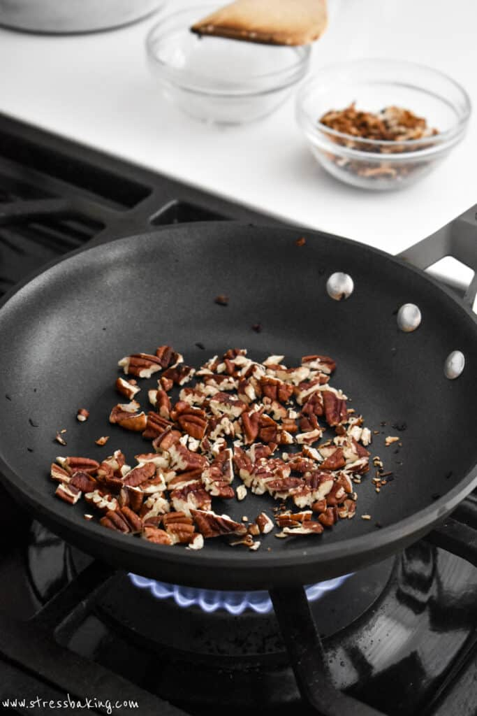 Pecan pieces being toasted in a saucepan