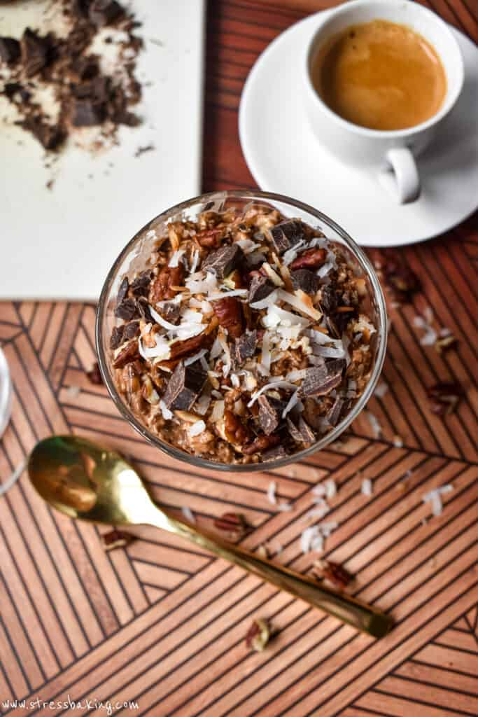 A small glass trifle dish with chocolate oats topped with pecans, coconut and chocolate chunks next to a cup of espresso
