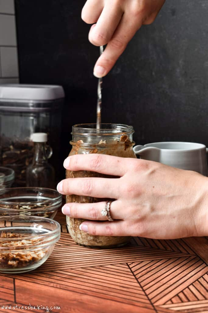 A mason jar of overnight oats being stirred on a retro wooden surface