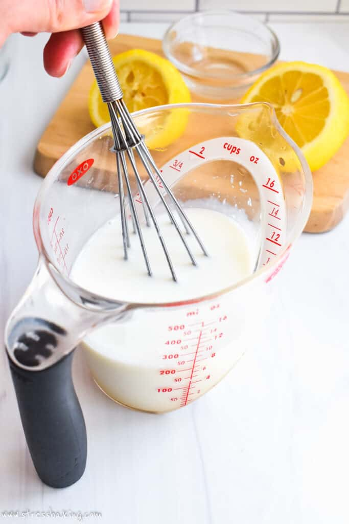 A whisk stirring a measuring cup of milk and lemon juice