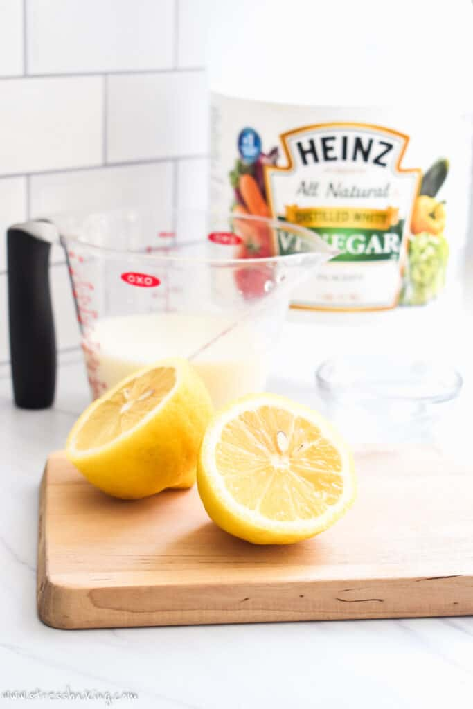 A sliced lemon on a small cutting board with a measuring cup of milk and jar of vinegar