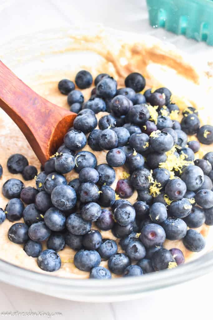 Vibrant blueberries in a glass bowl of batter with a wooden spoon