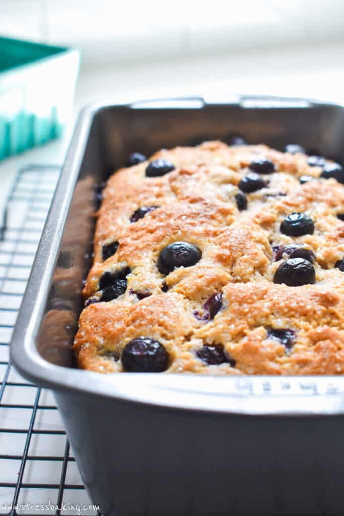 Side view of a loaf pan full of blueberry bread