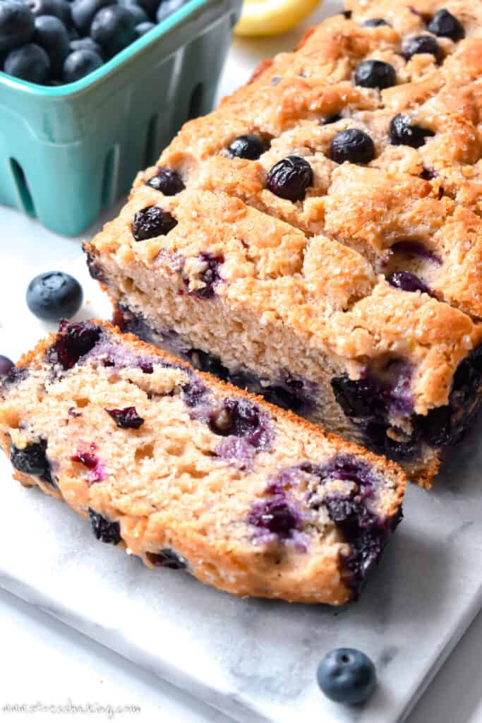 A loaf of blueberry muffin bread sliced on a marble platter