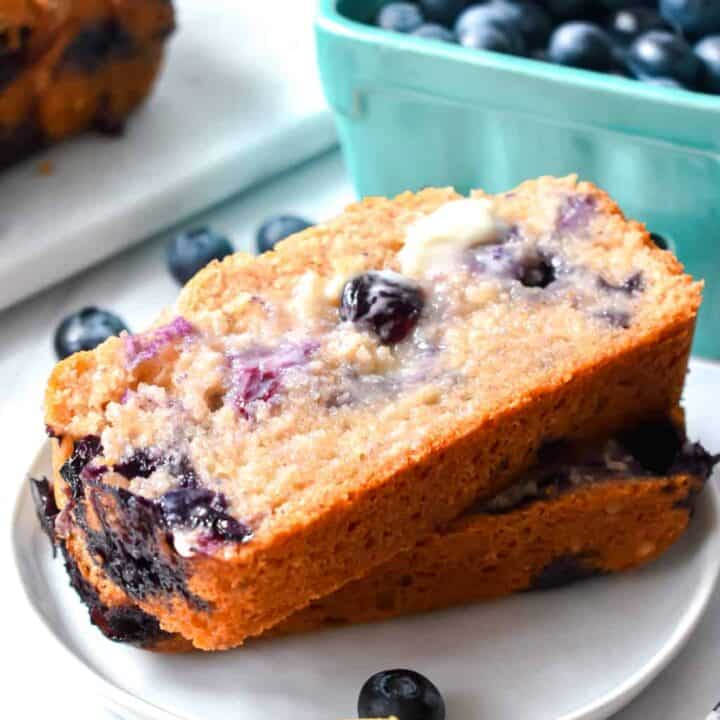Two slices of blueberry muffin bread slathered with butter on a white plate