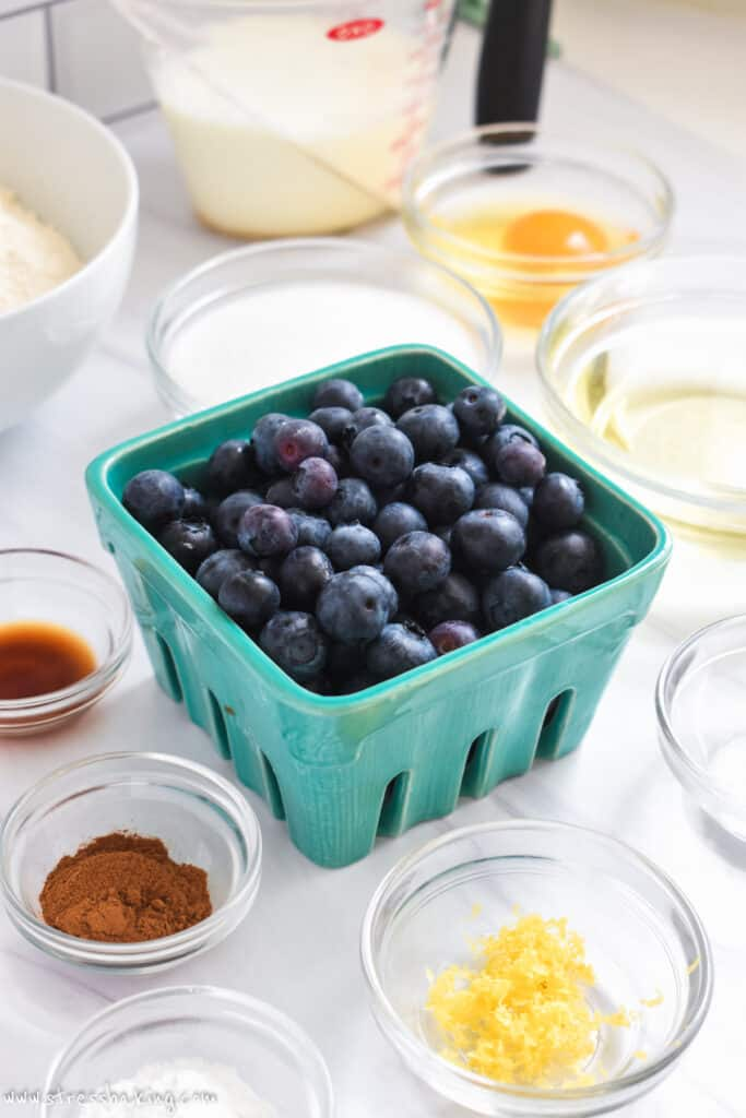 A teal container of blueberries surrounded by bowls of other ingredients for blueberry bread