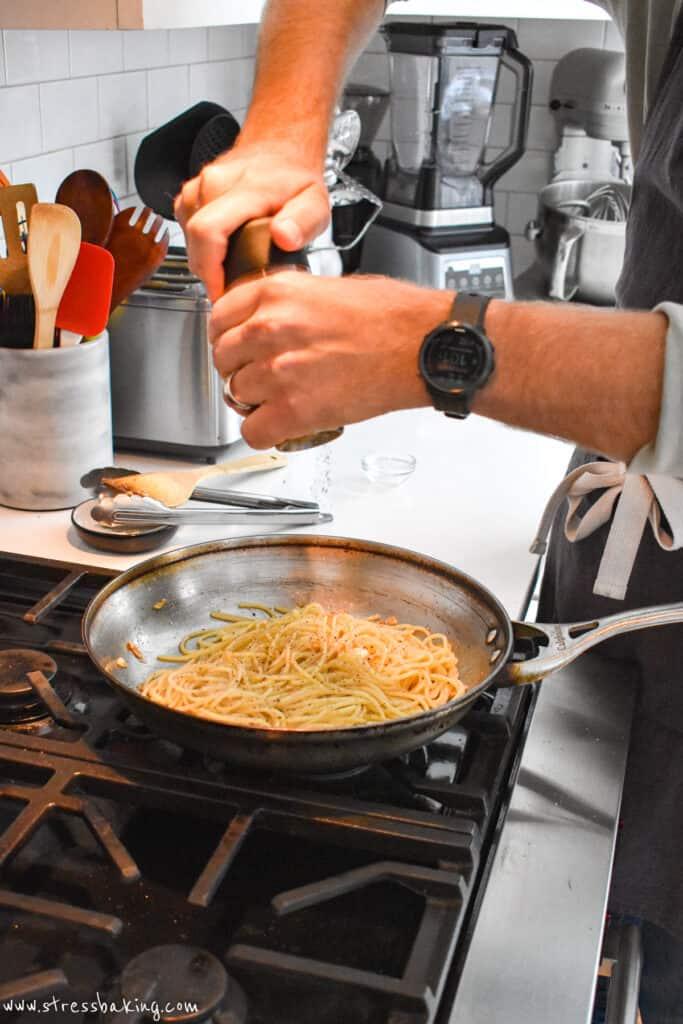 A man grinding fresh black pepper into a pan of spaghetti