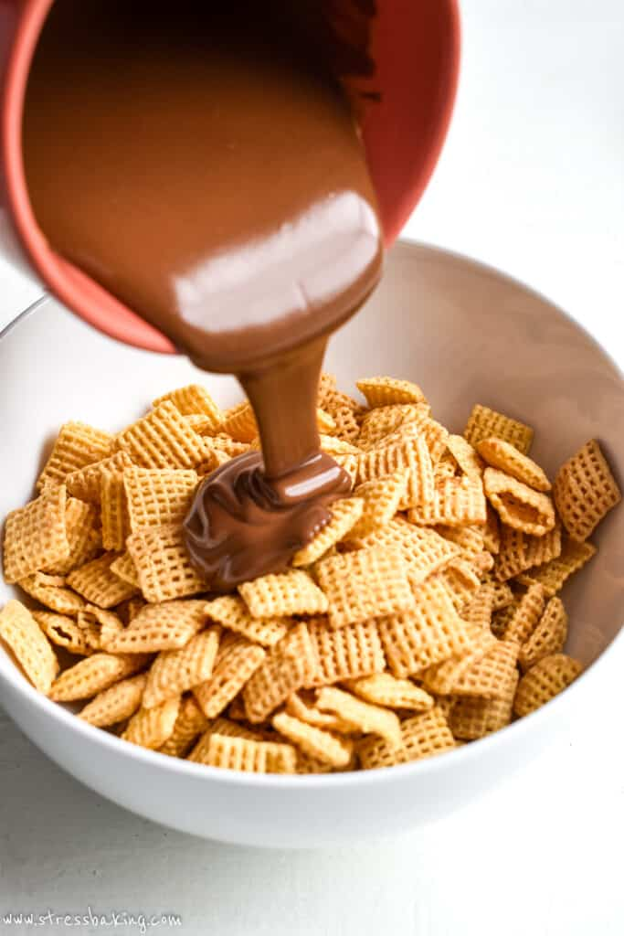 Melted chocolate being poured into a white bowl full of corn Chex cereal