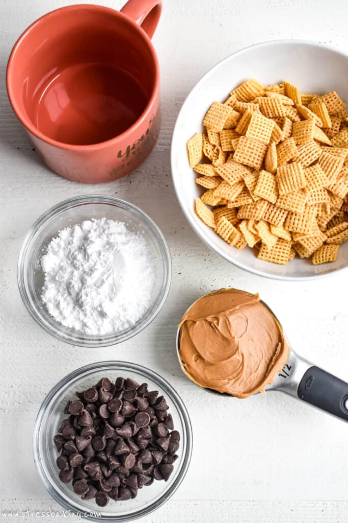 Ingredients for puppy chow in bowls on a white wood surface