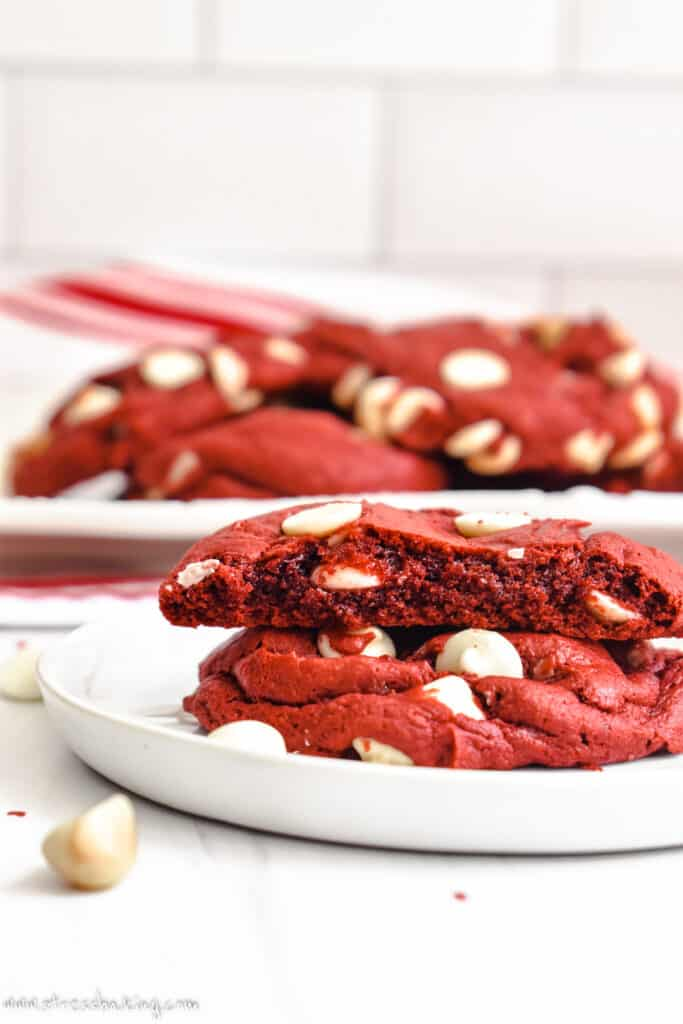 A red velvet cookies broken in half to show the soft middle on a small white plate