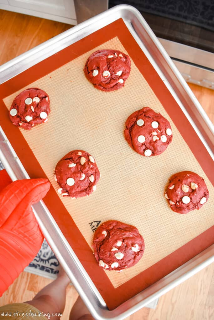 Freshly baked red velvet cookies with white chocolate chips on a baking sheet