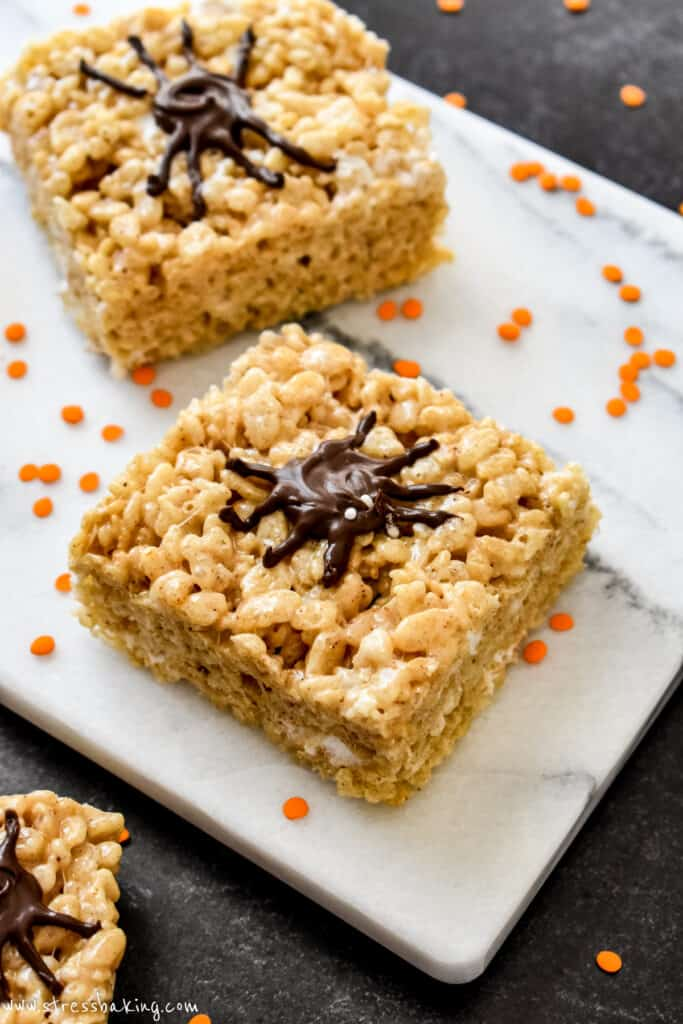 Halloween rice krispie treats with chocolate spiders decorating the tops surrounded by orange sprinkles