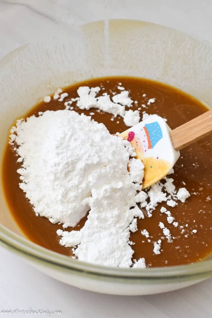 Powdered sugar about to be stirring into a caramel colored liquid