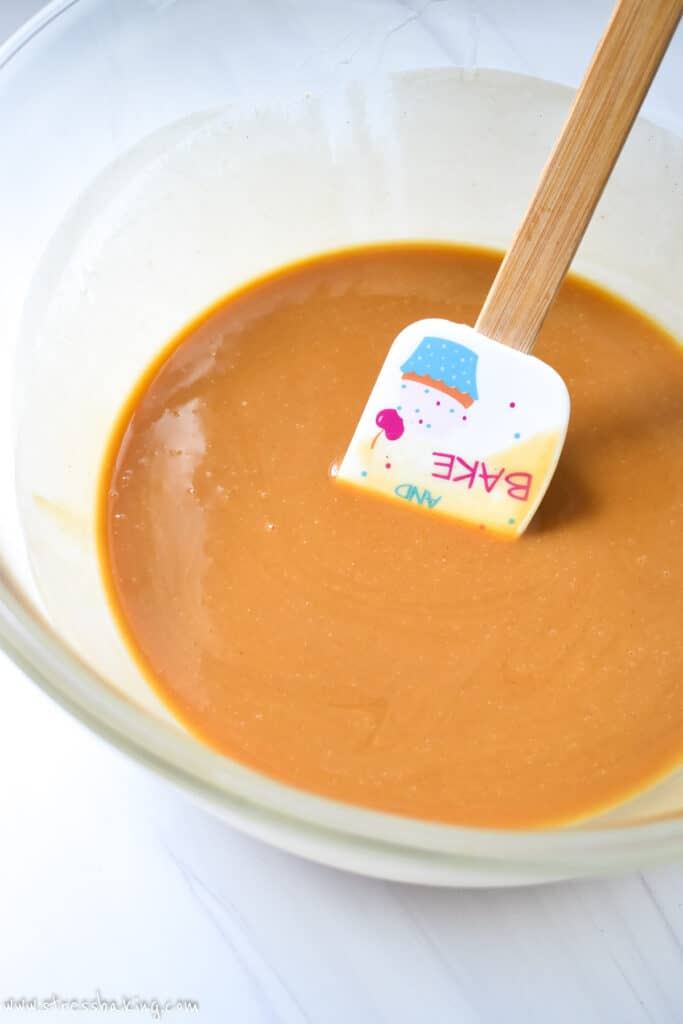 Caramel colored liquid in a clear mixing bowl with a colorful spatula