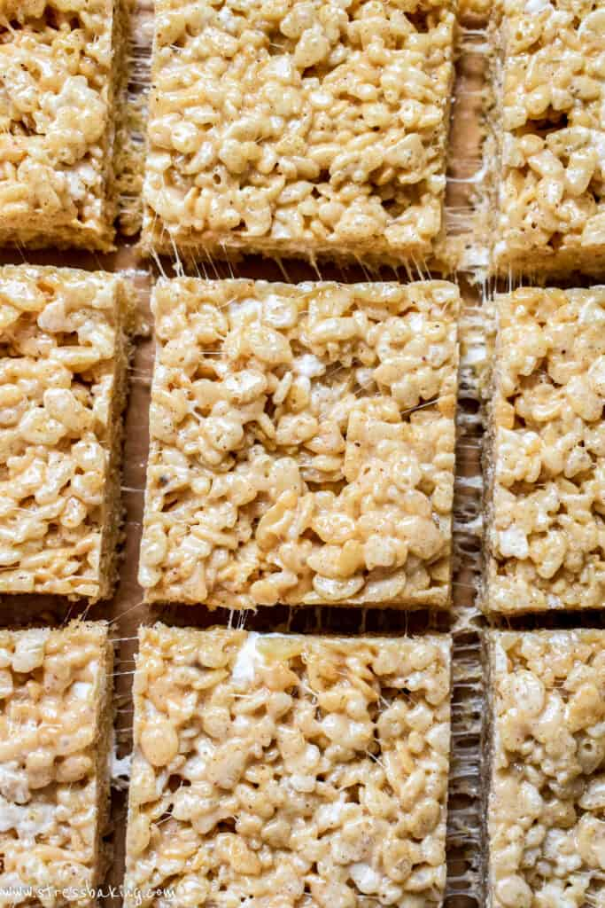 Pumpkin spice rice krispie treats that have been sliced and pulled apart to show their chewy marshmallow texture