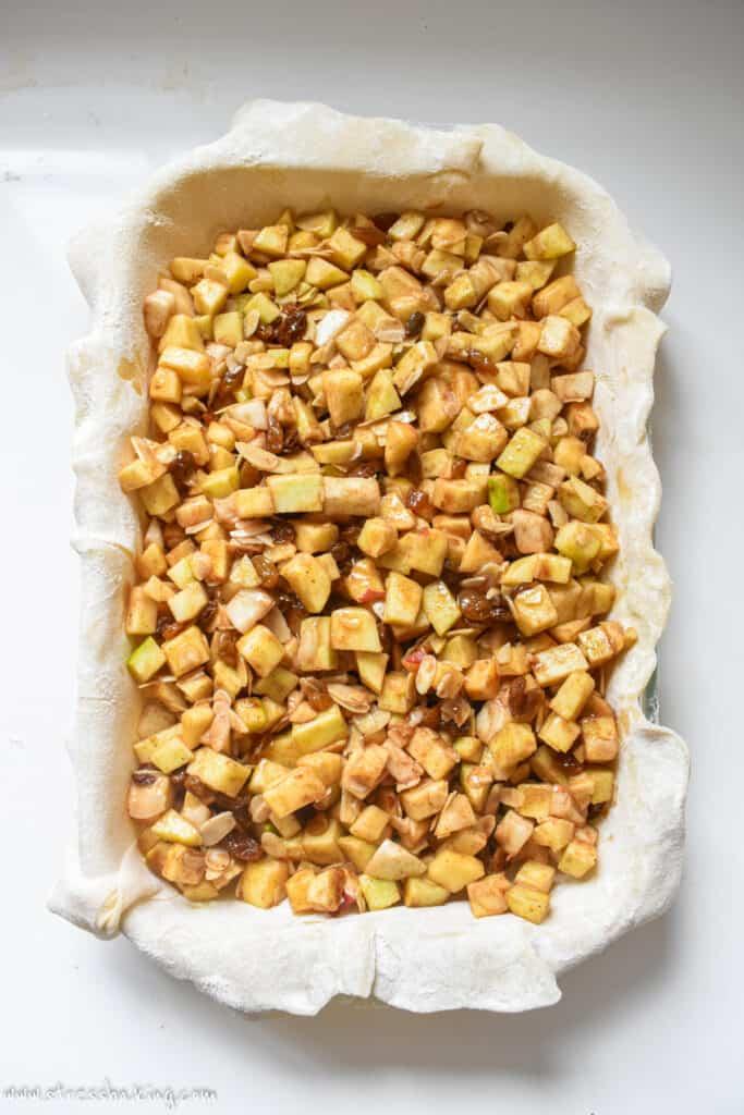 Diced apple filling inside a pie crust