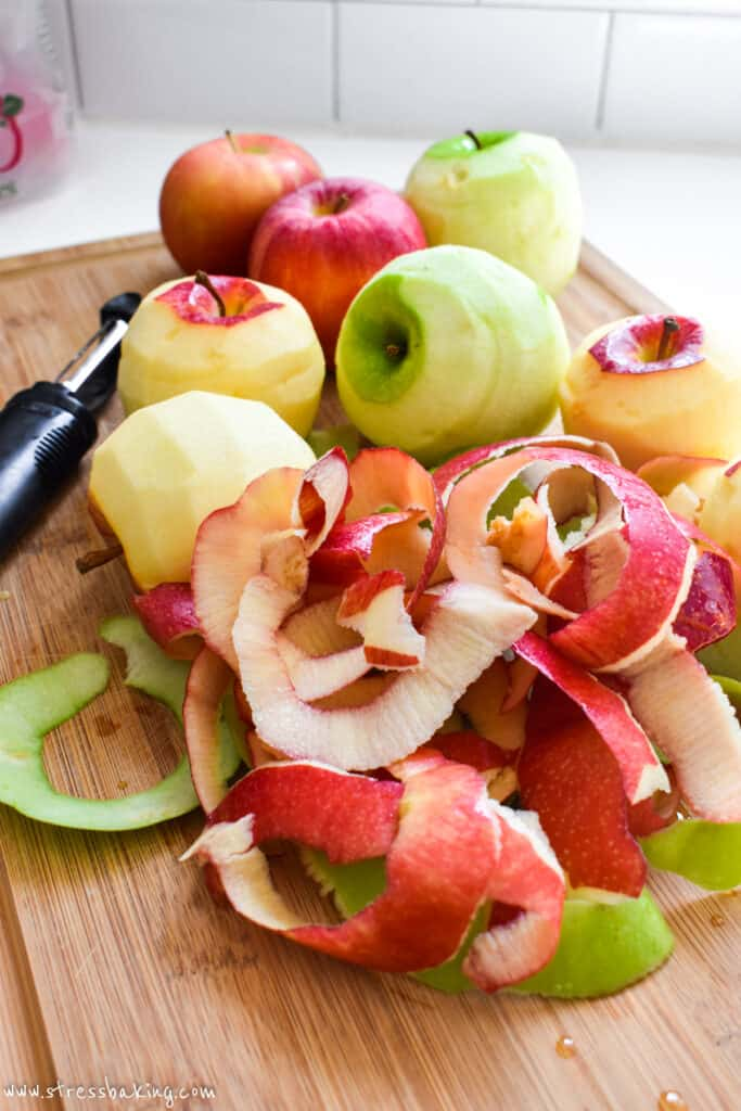 A pile of peeled apples on a cutting board