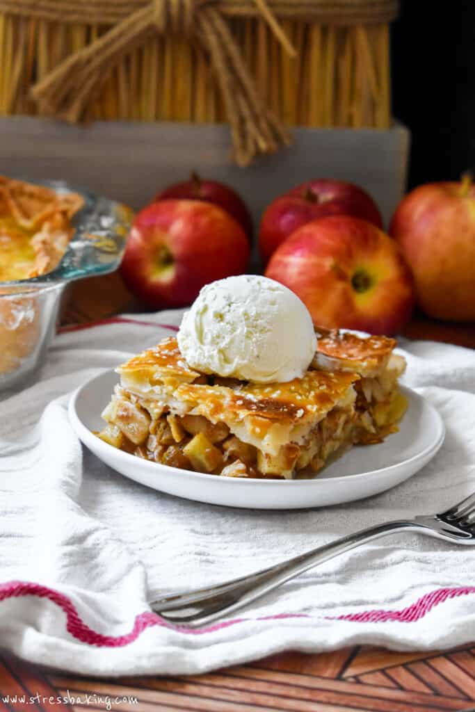 A huge slice of apple pie with a golden brown crust and topped with vanilla ice cream