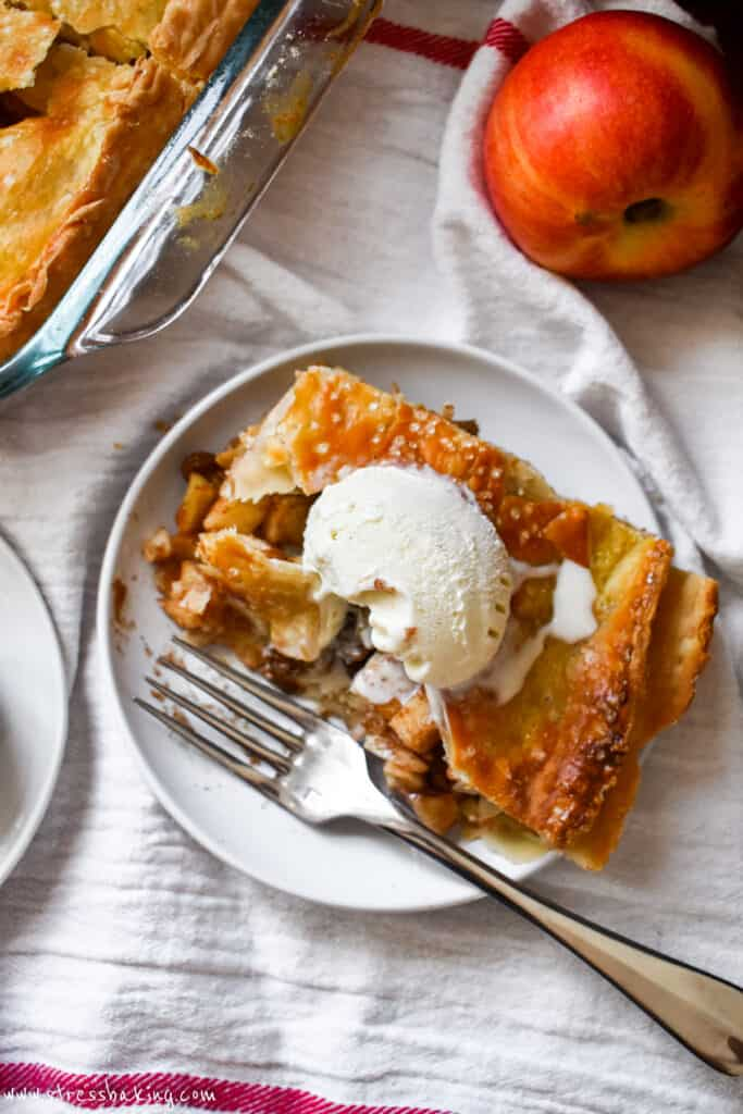 Overshot shot of a slice of apple pie with a golden brown crust and topped with vanilla ice cream