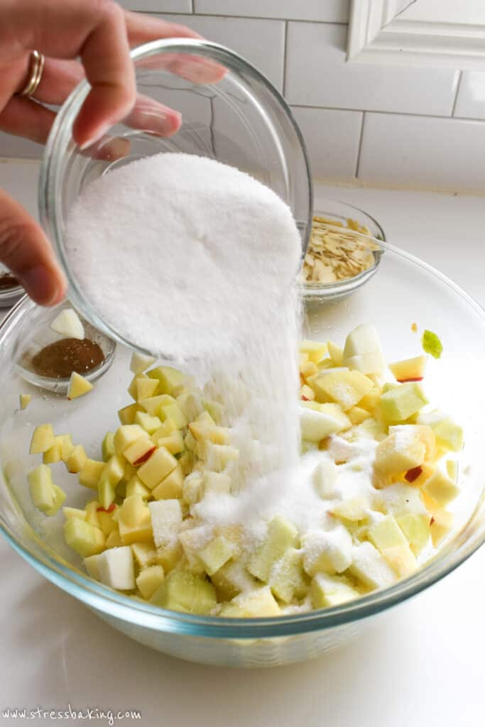 Granulated sugar being poured into a clear bowl of diced apples