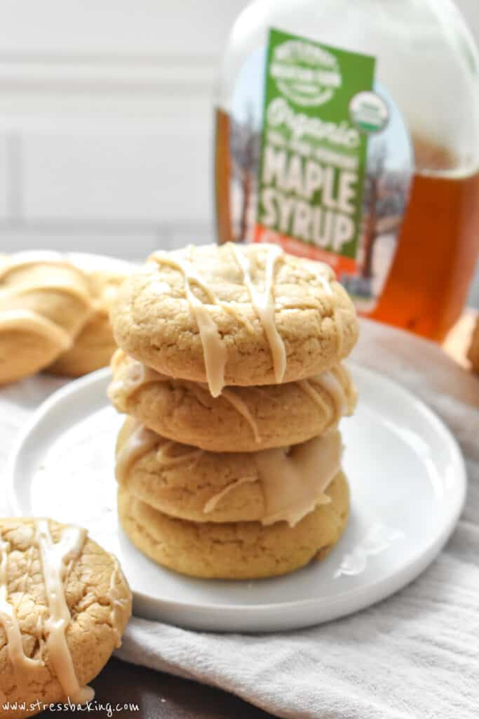 A stack of maple sugar cookies drizzled with icing on a white plate