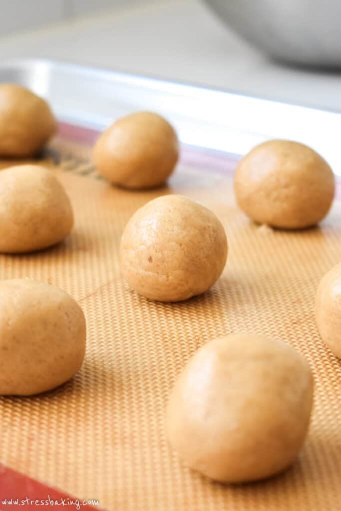 Smooth balls of tan colored dough on a baking sheet